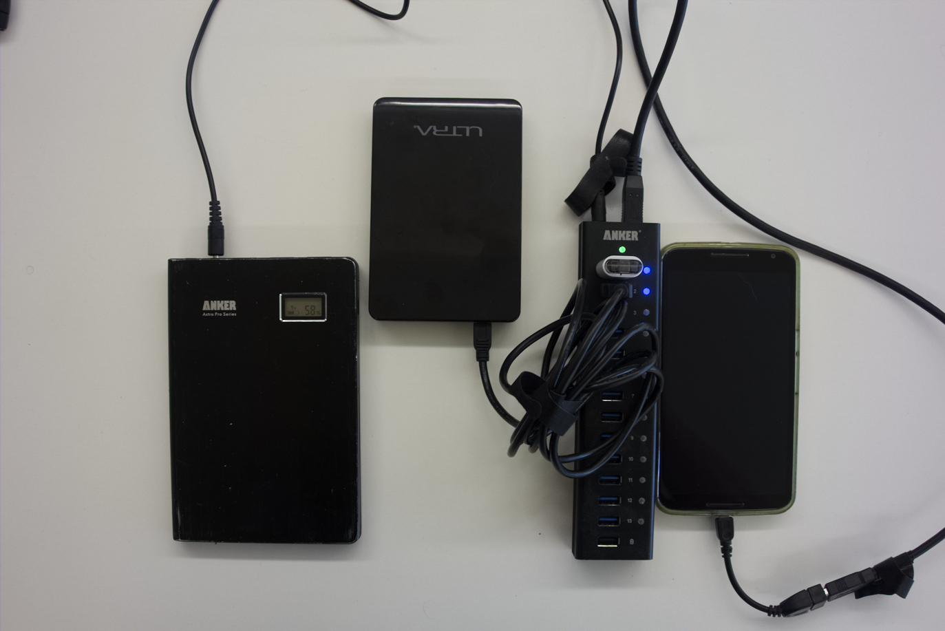 an external battery pack powering a USB hub with a disk drive, a flash drive, and a phone plugged into it.