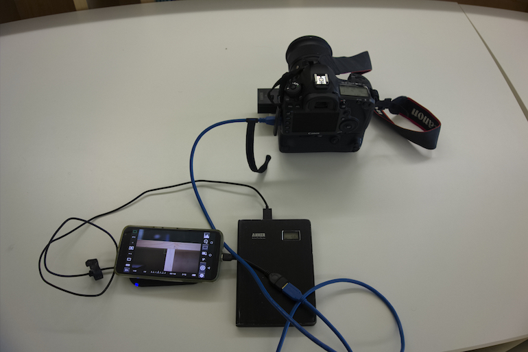 A camera connected to a cell phone, external battery, and Qi pad.