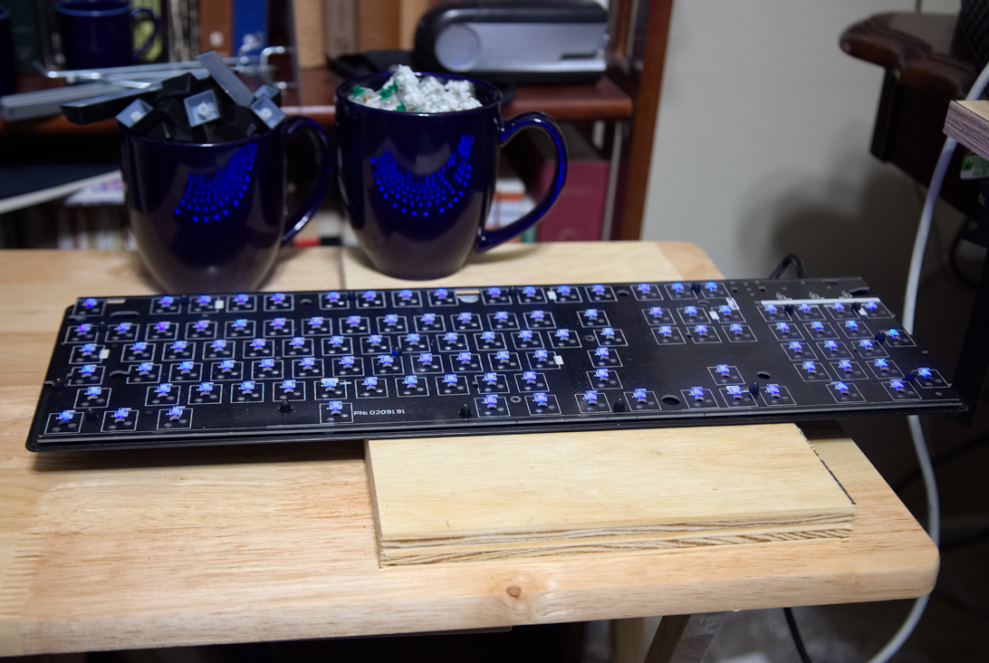 A picture of a keyboard PCB, with blue leds.  Two coffee cups with switches and keycaps behind it.