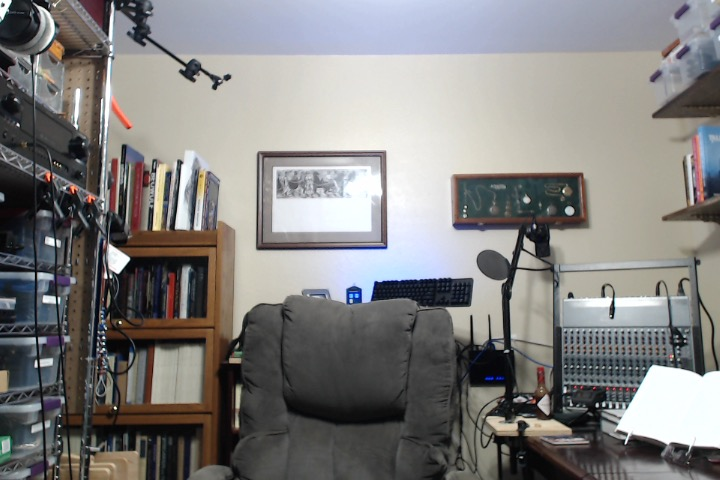 A webcam shot of an empty chair in an office with a bookshelf background.